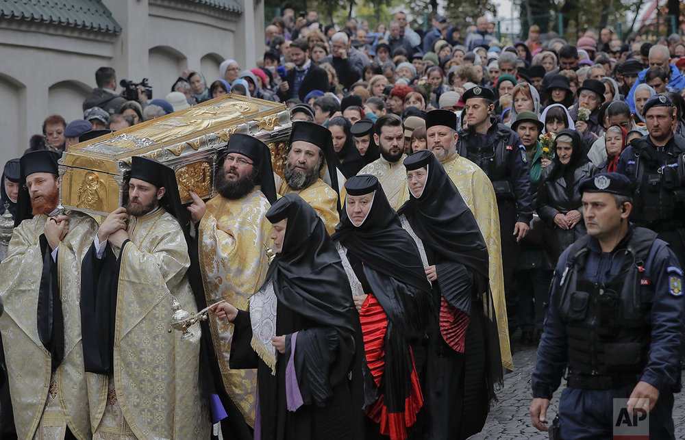 In this Saturday, Oct. 22, 2016 picture, priests carry the remains of Saint Dimitrie Bassarabov, during a pilgrimage, in Bucharest, Romania. (AP Photo/Vadim Ghirda)