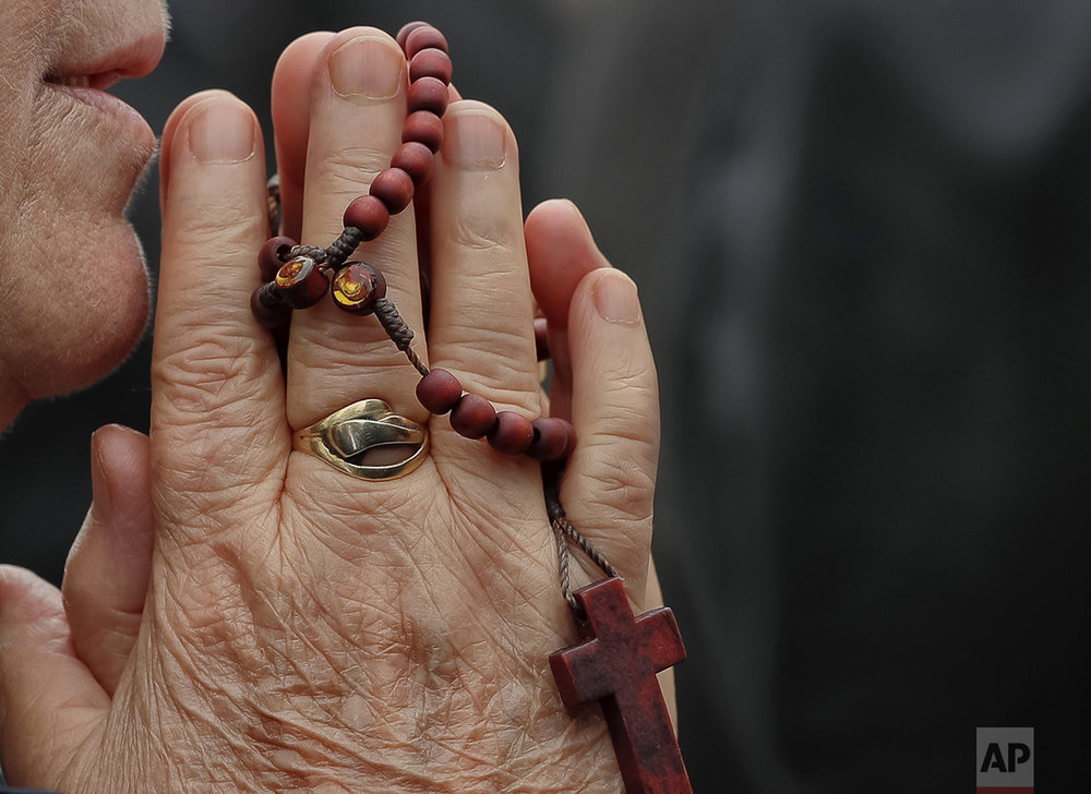 In this Sunday, Oct. 23, 2016 picture, a Catholic worshiper prays during a pilgrimage with Pope John Paul II's remains, in Bucharest, Romania. Both churches parade holy remains. The Catholics have a few drops of the blood of Saint John Paul II; the Orthodox claim to have the remains of three saints including those of St. Dimitrie, the patron saint of Bucharest. (AP Photo/Vadim Ghirda)