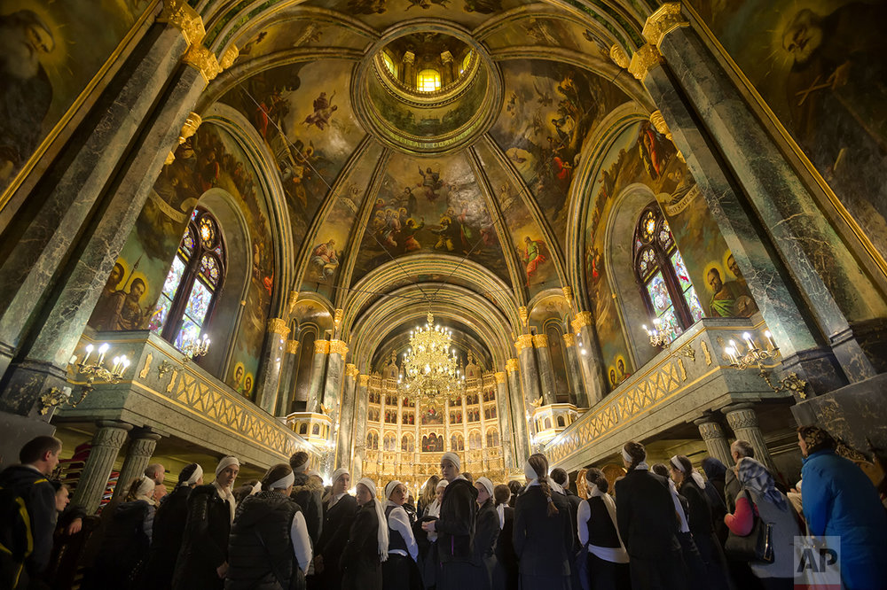 In this Saturday, Oct. 22, 2016 picture, Orthodox worshippers attend prayers in Bucharest, Romania. The Romanian Orthodox and Catholic churches staged pilgrimages parading holy remains. (AP Photo/Vadim Ghirda)