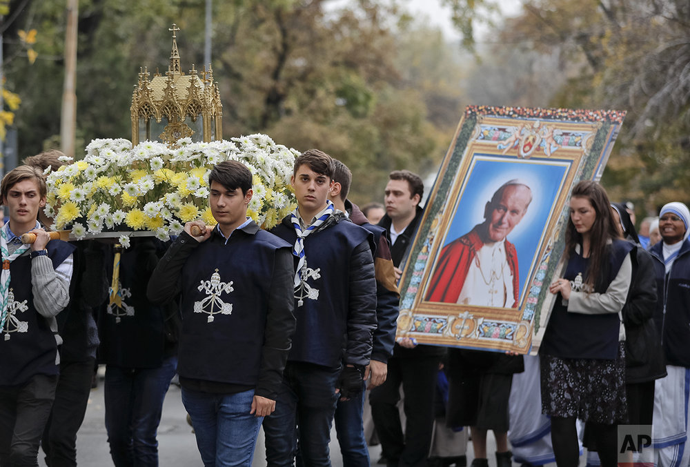 In this Sunday, Oct. 23, 2016 picture, Catholic worshipers take part in a pilgrimage with Pope John Paul II's remains, in Bucharest, Romania. The Romanian Orthodox and Catholic churches staged pilgrimages parading holy remains. (AP Photo/Vadim Ghirda)
