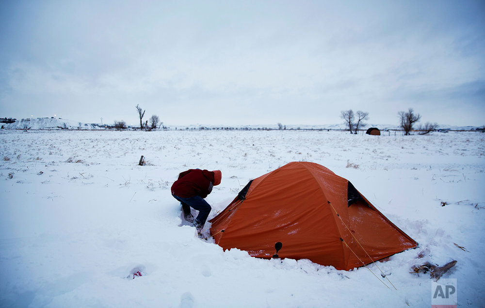 """In this Wednesday, Nov. 30, 2016 photo, Roy Tom of Ontario, Canada, and a member of the Ojibwa Native American tribe clears away snow from his tent where he's lived for over two months at the Oceti Sakowin camp where people have gathered to protest the Dakota Access oil pipeline, in Cannon Ball, N.D. """"You have to get used to it,"""" Tom said of the snow and cold weather. (AP Photo/David Goldman)"""