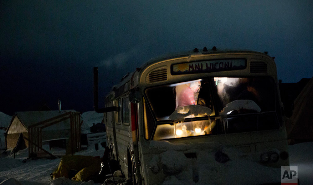 In this Wednesday, Nov. 30, 2016 photo, a person is seen inside a bus turned into a camper at the Oceti Sakowin camp where people have gathered to protest the Dakota Access pipeline near Cannon Ball, N.D. The camp covers a half square mile, with living quarters that include old school buses, fancy motorhomes and domelike yurts. Hay bales are piled around some teepees to keep out the wind. There's even a crude corral for horses. (AP Photo/David Goldman)