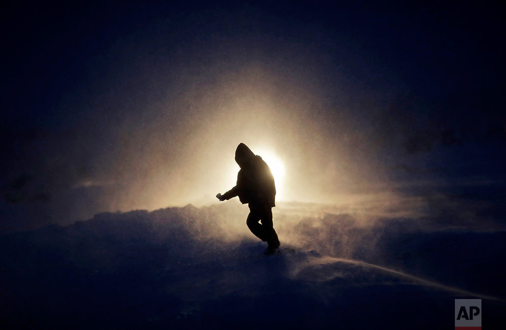 In this Tuesday, Nov. 29, 2016, photo, a person walks through a snow storm at the Oceti Sakowin camp where people have gathered to protest the Dakota Access oil pipeline in Cannon Ball, N.D. Those in the camp have shrugged off the heavy snow, icy winds and frigid temperatures. But if they defy next week's government deadline to abandon the camp, demonstrators know the real deep freeze lies ahead. (AP Photo/David Goldman)