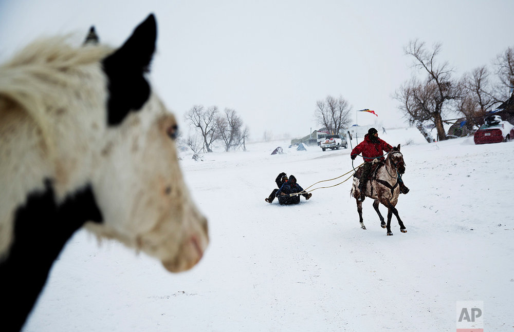 In this Tuesday, Nov. 29, 2016 photo, Smokey, a member of the Sioux Native American tribe, rides the horse Prophecy, a descendant of the horse belonging to war chief Crazy Horse, as he pulls a sled at the Oceti Sakowin camp where people have gathered to protest the Dakota Access oil pipeline, in Cannon Ball, N.D. The government has ordered protesters to leave federal land by Monday, but they insist they will stay for as long it takes to divert the $3.8 billion pipeline. (AP Photo/David Goldman)
