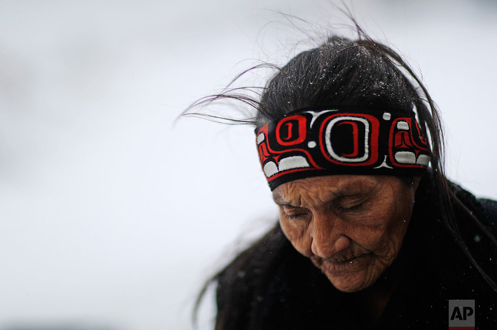 """In this Tuesday, Nov. 29, 2016 photo, Grandma Redfeather of the Sioux Native American tribe walks in the snow to get water at the Oceti Sakowin camp where people have gathered to protest the Dakota Access oil pipeline in Cannon Ball, N.D. """"It's for my people to live and so that the next seven generations can live also,"""" said Redfeather of why she came to the camp. """"I think about my grandchildren and what it will be like for them."""" (AP Photo/David Goldman)"""