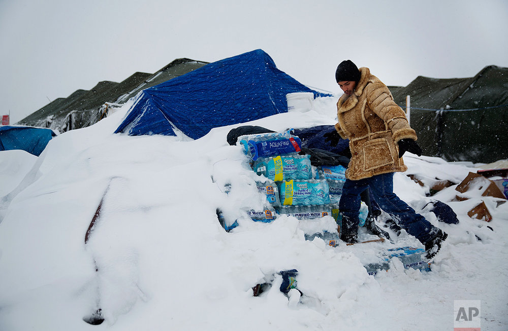 In this Tuesday, Nov. 29, 2016 photo, Lawrence Valdez, of New Mexico and a member of the Chiricahua Apache Native American tribe, drops off bottles of water at the Oceti Sakowin camp where people have gathered to protest the Dakota Access oil pipeline, in Cannon Ball, N.D. Camp dwellers are getting ready for the hardships of a long stay. Mountains of donated food and water are being stockpiled, as is firewood, much of which has come from outside of North Dakota, the least-forested state in the nation. (AP Photo/David Goldman)