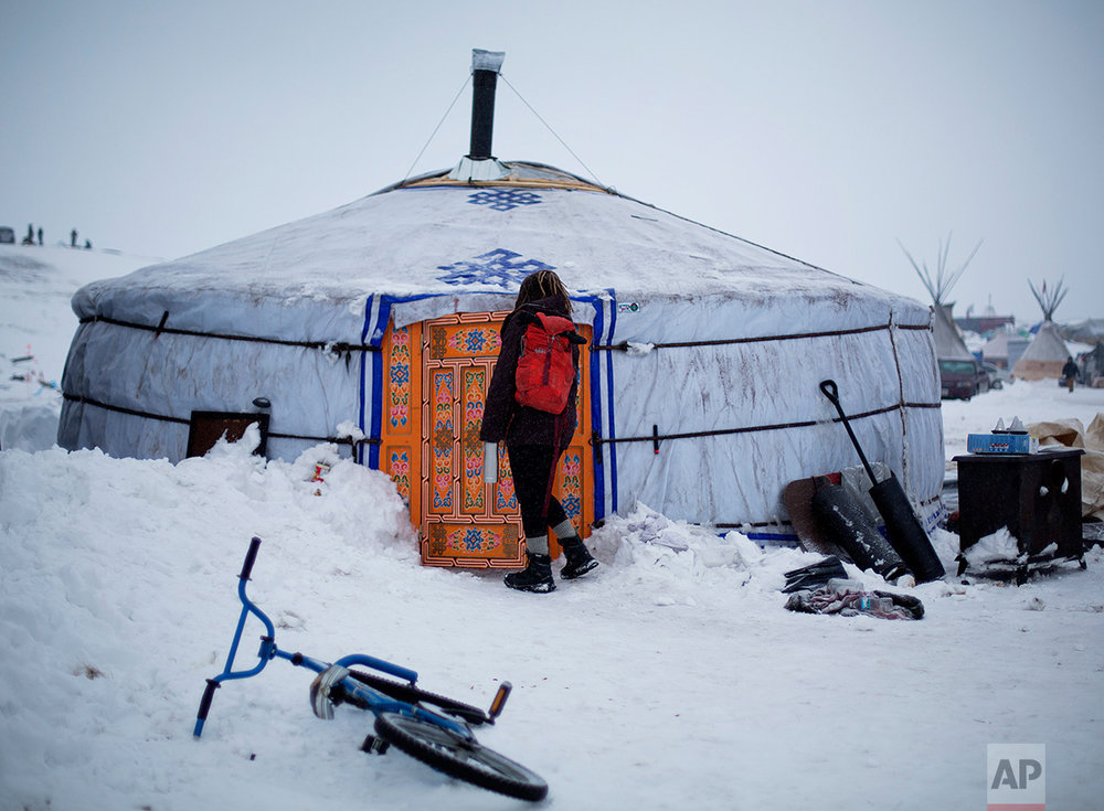 In this Thursday, Dec. 1, 2016 photo, a student walks into the school at the Oceti Sakowin camp where people have gathered to protest the Dakota Access pipeline near Cannon Ball, N.D. The school teaches on average 20 students a day in the traditional Lakota curriculum as well as math, reading and writing. (AP Photo/David Goldman)