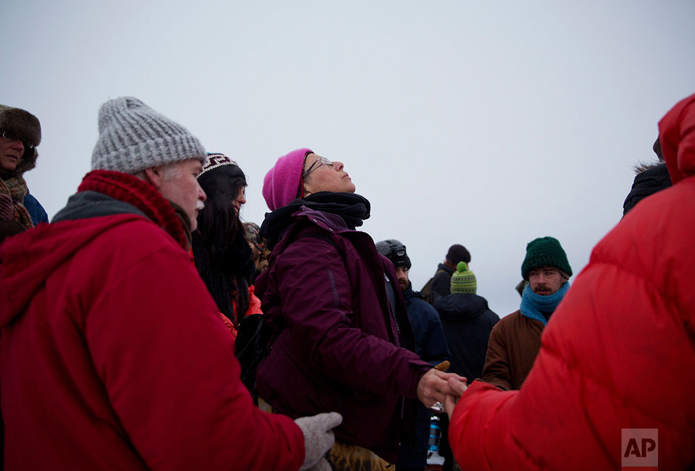 In this Thursday, Dec. 1, 2016 photo, Elena Ruben Goodman, of Oakland, Calif., waits her turn to pray by the Cannonball river during a Native American water ceremony at the Oceti Sakowin camp where people have gathered to protest the Dakota Access oil pipeline in Cannon Ball, N.D. On Thursday, the camp near the confluence of the Missouri and Cannonball rivers was shrouded in snow, much of it compacted by foot and vehicle traffic. Next week's forecast calls for single digits and subzero wind chills. (AP Photo/David Goldman)