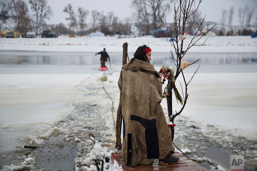 In this Thursday, Dec. 1, 2016 photo, Cat Bigney, part of the Oglala Native American tribe, waits on the shore of the Cannonball river for travelers to arrive by canoe at the Oceti Sakowin camp where people have gathered to protest the Dakota Access oil pipeline in Cannon Ball, N.D. So far, those at the camp have shrugged off the heavy snow, icy winds and frigid temperatures. But if they defy next week's government deadline to abandon the camp, demonstrators know the real deep freeze lies ahead. Life-threatening wind chills and towering snow drifts could mean the greatest challenge is simple survival. (AP Photo/David Goldman)