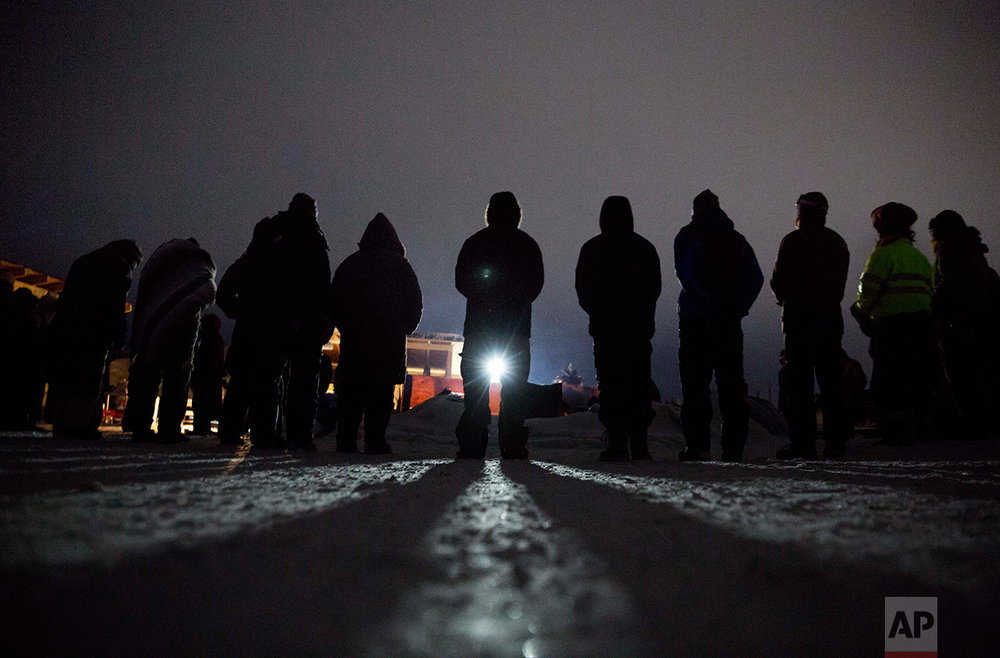 In this Wednesday, Nov. 30, 2016 photo, people form a circle for the morning prayer at the Oceti Sakowin camp where many have gathered to protest the Dakota Access pipeline near Cannon Ball, N.D. The number of inhabitants has ranged from several hundred to several thousand. It has been called the largest gathering of Native American tribes in a century. (AP Photo/David Goldman)