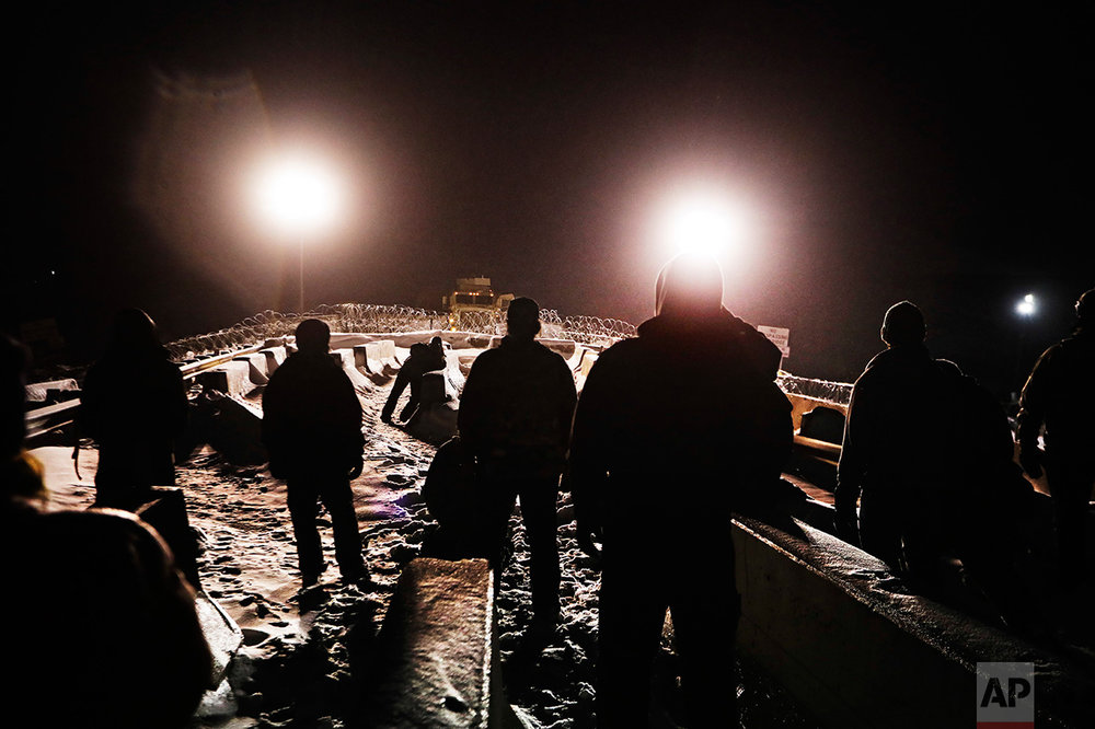 In this Thursday, Dec. 1, 2016 photo, military veterans walk onto a closed bridge to protest across from police protecting the Dakota Access oil pipeline site in Cannon Ball, N.D. More than 525 people from across the country have been arrested since August. In a recent clash between police and protesters near the path of the pipeline, officers used tear gas, rubber bullets and large water hoses in sub-freezing temperatures. (AP Photo/David Goldman)