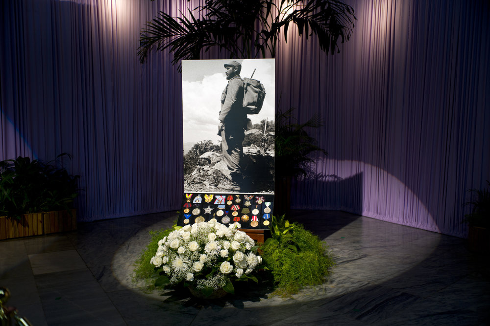 In this Nov. 28, 2016 photo, roses and medals serve as a base for a portrait of the late Fidel Castro at Revolution Plaza, the site of two days of tributes to the late leader, in Havana, Cuba. Cubans bid farewell to Castro, the man who ruled the island for nearly half a century. Cuba's declared nine days of national mourning following Castro's death Friday night at age 90. (AP Photo/Ramon Espinosa)