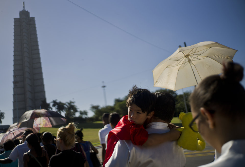 In this Nov. 29, 2016 photo, a man holds a child as he waits in line to visit the memorial site for the late Cuban leader Fidel Castro at the Revolution Plaza in Havana, Cuba. Schools and government offices closed in homage to Fidel Castro, with the day ending in a rally on the wide plaza where the Cuban leader delivered fiery speeches to mammoth crowds in the years after he seized power. (AP Photo/Ramon Espinosa)