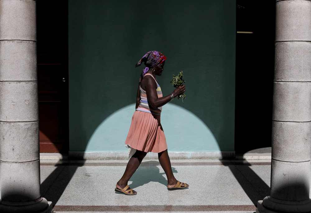In this Nov. 29, 2016 photo, a woman arrives at a memorial in honor of late Cuban leader Fidel Castro, holding a bouquet of flowers, in Guanabacoa on the outskirts in Havana, Cuba. President Raul Castro said Cuba would bar statues of Castro and monuments bearing his name in keeping with the former leader's desire to prevent the growth of a cult of personality. (AP Photo/Natacha Pisarenko)