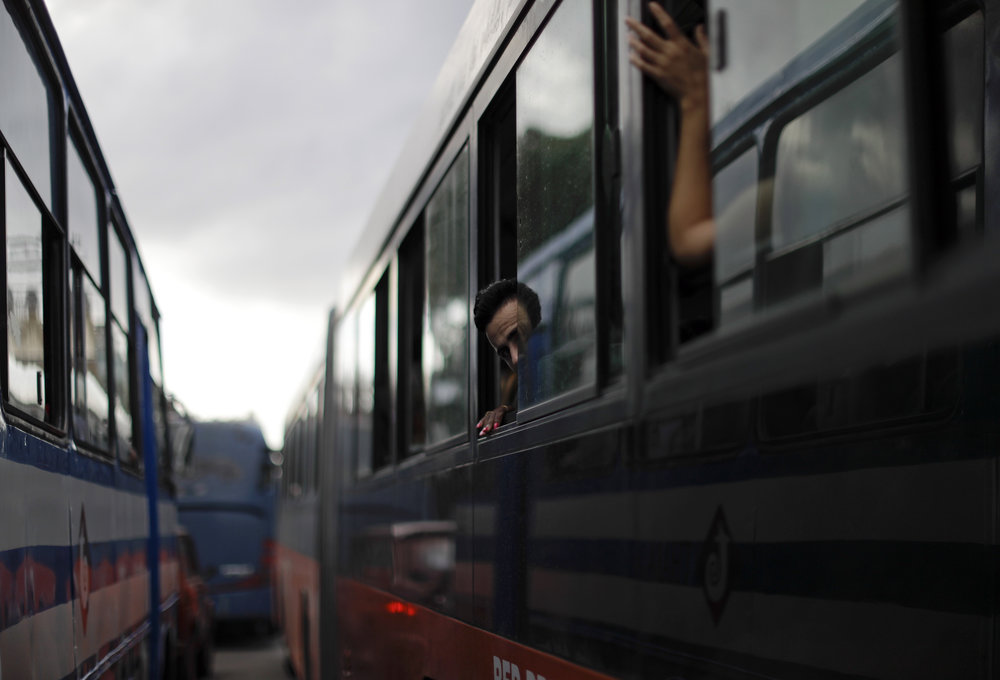 In this Nov. 29, 2016 photo, a man peeks out of a bus window as he arrives to attend a massive rally honoring the late Cuban leader Fidel Castro at Revolution Plaza in Havana, Cuba. Schools and government offices were closed in homage to Fidel Castro, with the day ending in a rally on the wide plaza where the Cuban leader delivered fiery speeches to mammoth crowds in the years after he seized power. (AP Photo/Natacha Pisarenko)
