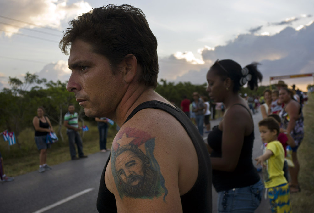 In this Nov. 30, 2016 photo, a man with a tattoo of Cuba's late leader Fidel Castro waits for the arrival of the caravan carrying his ashes during a funeral procession that retraces the path of Castro's triumphant march into Havana nearly six decades ago, in Cruces, Cuba. Castro's ashes completed in Santa Clara the first leg of a cross-country trip, a four-day journey across Cuba from Havana to their final resting place in the eastern city of Santiago. (AP Photo/Ramon Espinosa)