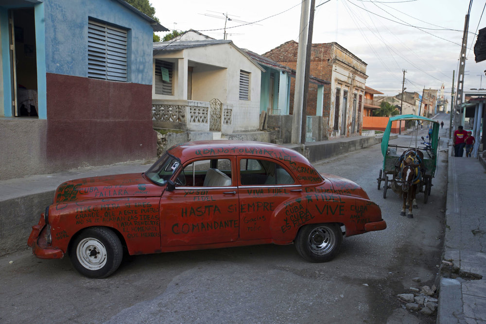 In this Nov. 30, 2016 photo, a car covered with messages to Cuba's leader Fidel Castro is parked in La Esperanza, Cuba. Castro's ashes journeyed in a funeral procession that retraced the path of his triumphant march into Havana nearly six decades ago in a four-day journey across Cuba from the capital to their final resting place in the eastern city of Santiago. President Raul Castro said Cuba would bar statues of Castro and monuments bearing his name in keeping with the former leader's desire to prevent the growth of a cult of personality. (AP Photo/Ricardo Mazalan)