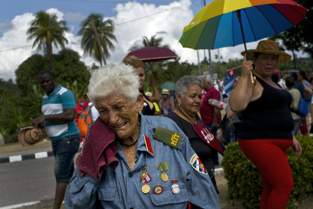 In this Dec. 3, 2016 photo, a former combatant of the Revolutionary Army, Paulina Ballard, 81, weeps after watching the funeral procession carrying the ashes of Cuba's late leader Fidel Castro arrive in Santiago, Cuba. After a four-day journey across the country through small towns and cities where his rebel army fought its way to power nearly 60 years ago, Castro's remains were interred in Santiago. (AP Photo/Ramon Espinosa)