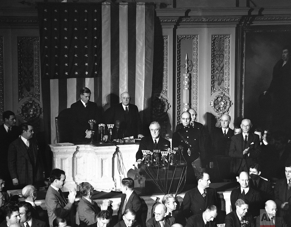 Declaring Japan guilty of a dastardly unprovoked attack, President Franklin D. Roosevelt asked Congress to declare war, Dec. 8, 1941. Listening are Vice President Henry Wallace, left, and House Speaker Sam Rayburn. (AP Photo)