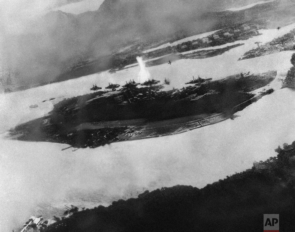 Believed to be the first bomb dropped on Pearl Harbor, Hawaii in the sneak-attack on Dec. 7, 1941, this picture was found torn to pieces at Yokusuka Base by photographer's mate 2/C Martin J. Shemanski of Plymouth, Pa. One Japanese plane is shown pulling out of a dive near bomb eruption (center) and another the air at upper right. (AP Photo)