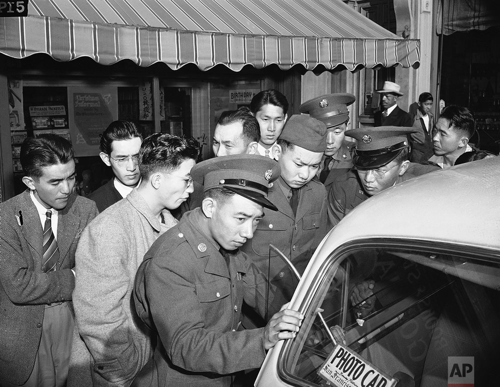 Young Japanese Americans, including several Army selectees, gather around a reporter's car in the Japanese section of San Francisco, Dec. 8, 1941. (AP Photo)