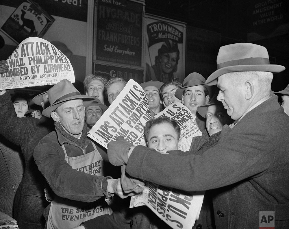 In this Dec. 7, 1941 photo, people buy newspapers reporting the Japanese attack on U.S. bases in the Pacific Ocean, at Times Square in New York. (AP Photo/Robert Kradin)