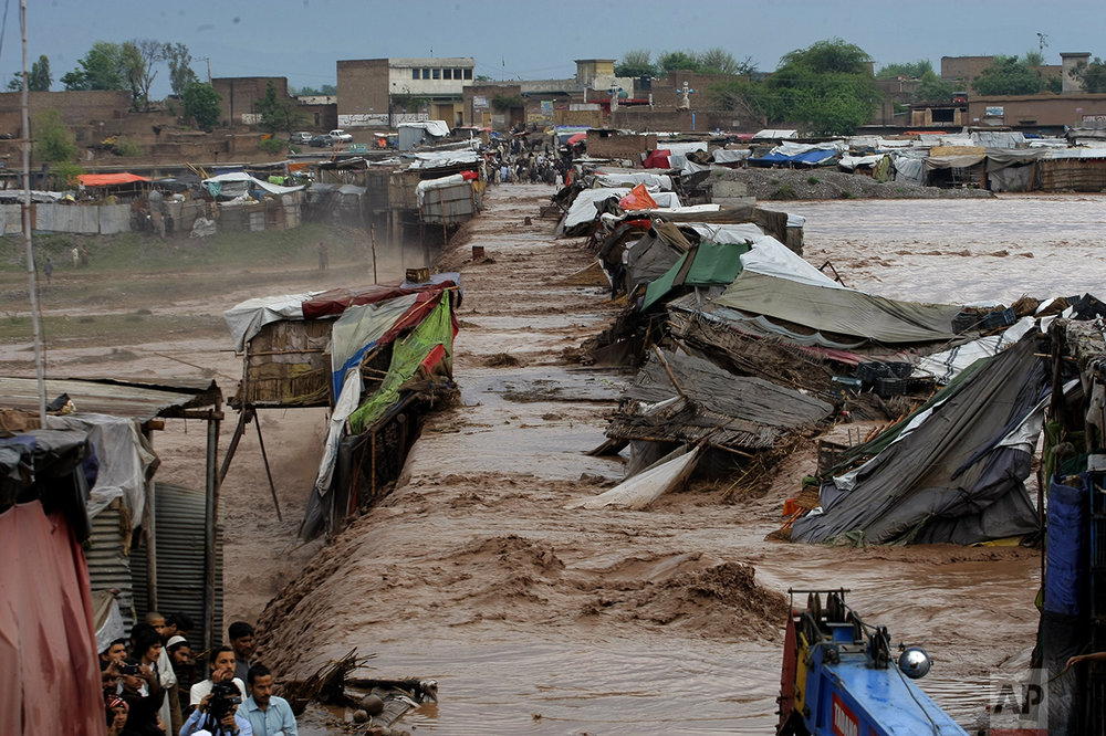 Villagers stand outside their homes during flash floods on the outskirts of Peshawar, Pakistan, on April 3, 2016. (AP Photo/Mohammad Sajjad)