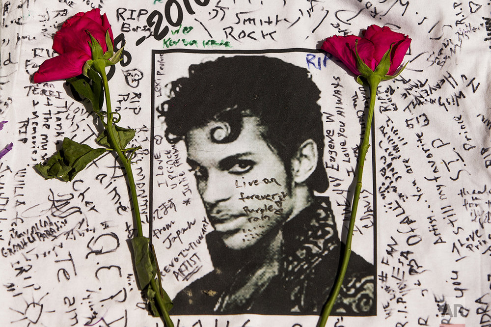 Flowers lie on a T-shirt signed by fans of singer Prince at a makeshift memorial place created outside the Apollo Theater in New York on April 22, 2016. The pop star died at the age of 57. (AP Photo/Andres Kudacki)