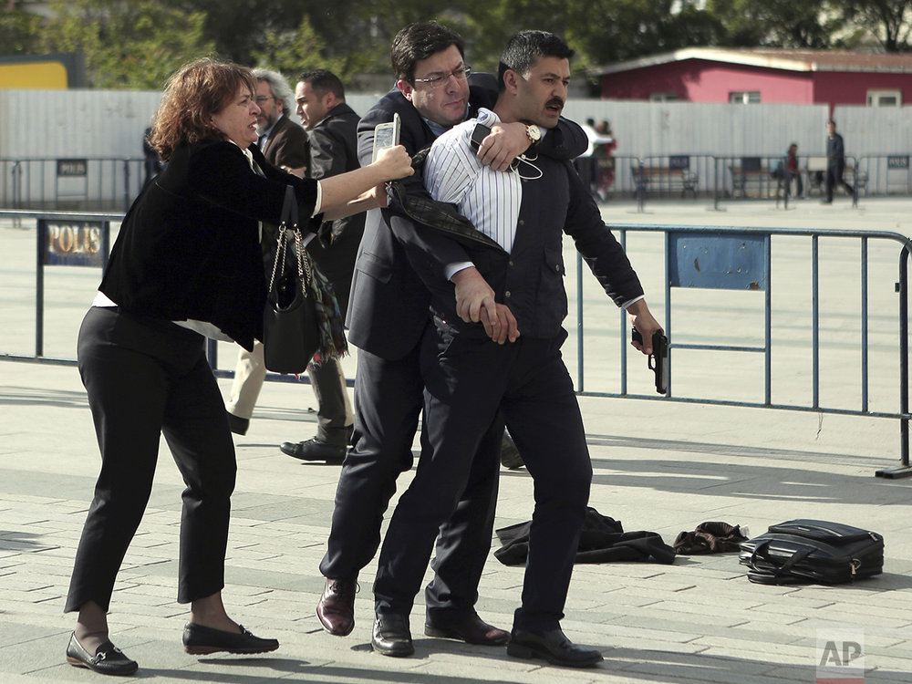 "Dilek Dundar, wife of journalist Can Dundar, and his lawyer, second left, overpower a gunman just after he attacked Can Dundar outside Istanbul's main courthouse on May 6, 2016. The man shouted ""traitor"" and fired two shots at Dundar, who was on trial accused of revealing state secrets for his reports on alleged government arms smuggling to Syria. Dundar, editor-in-chief of opposition Cumhuriyet newspaper, escaped the attack unhurt, but Yavuz Senkal, a journalist working for private NTV television was slightly injured in the leg. (Can Erok/Cumhuriyet via AP)"