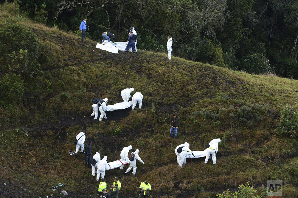 Rescue workers carry the bodies of victims of an airplane crash in a mountainous area near La Union, Colombia, on Nov. 29, 2016. The plane was carrying the Brazilian first division soccer club Chapecoense team, which was on its way for a Copa Sudamericana final match against Colombia's Atletico Nacional. (AP Photo/Luis Benavides)