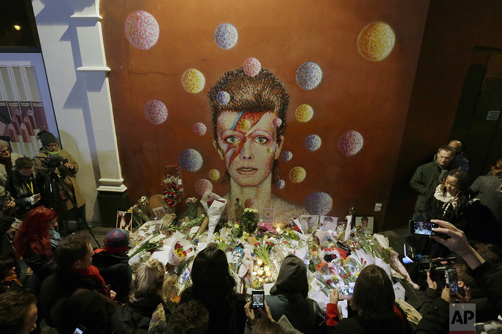 People gather next to tributes placed near a mural of British singer David Bowie by artist Jimmy C, in Brixton, south London, on Jan. 11, 2016. Bowie, the other-worldly musician who broke pop and rock boundaries with his creative musicianship, nonconformity, striking visuals and a genre-spanning persona he christened Ziggy Stardust, died of cancer at age 69. He was born in Brixton. (AP Photo/Tim Ireland)