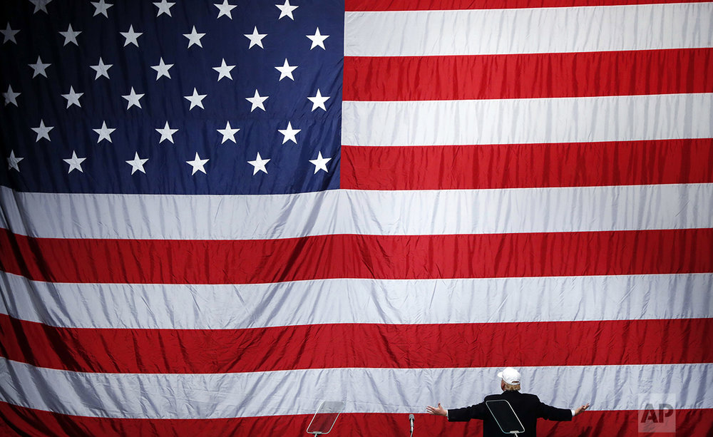 Republican presidential candidate Donald Trump turns to the American flag at a campaign rally in Sterling Heights, Mich., on Nov. 6, 2016. (AP Photo/Paul Sancya)