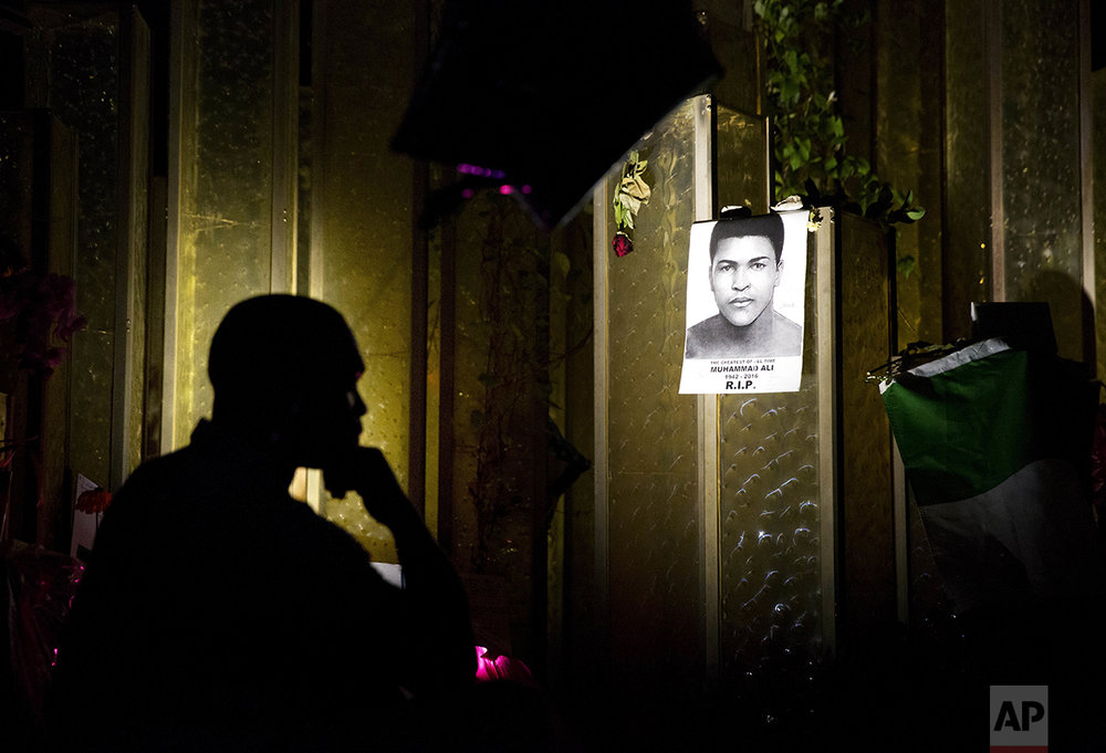 A visitor to the Muhammad Ali Center in Louisville, Ky., looks at an image of the great boxer posted on a makeshift memorial on June 9, 2016. Ali, born Cassius Clay, died on June 3 at age 74. (AP Photo/David Goldman)
