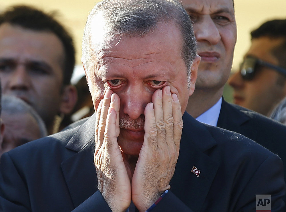 Turkish President Recep Tayyip Erdogan, right, wipes his tears during the funeral of Mustafa Cambaz, Erol and Abdullah Olcak, killed while protesting the attempted coup against Turkey's government, in Istanbul on July 17, 2016. (AP Photo/Emrah Gurel)
