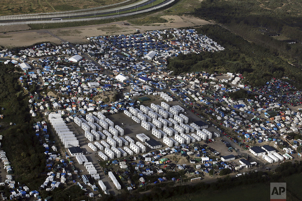 An aerial view shows a makeshift migrant camp near Calais, France, on Oct. 17, 2016. The French evacuated 6,400 migrants from the encampment in 170 buses, starting on Oct. 24, 2016, with the intent of resettling the migrants in different regions of France. On Oct. 26 French authorities announced that the camp had been cleared. (AP Photo/Thibault Camus)