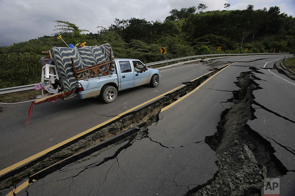 A truck moves the belongings of a family over a road destroyed by an earthquake from Pedernales to Jama, Ecuador, on April 18, 2016. The earthquake left a trail of ruin along Ecuador's Pacific Ocean coast. Hundreds died, thousands were homeless and without electricity. (AP Photo/Dolores Ochoa)