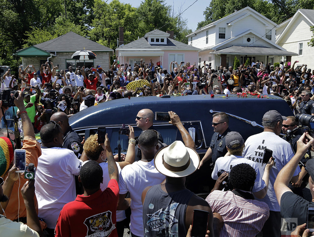 The hearse carrying the body of Muhammad Ali passes in front of his boyhood home, top center, during his funeral procession in Louisville, Ky., on June 10, 2016. Ali, born Cassius Clay, died on June 3 at age 74. (AP Photo/Mark Humphrey)