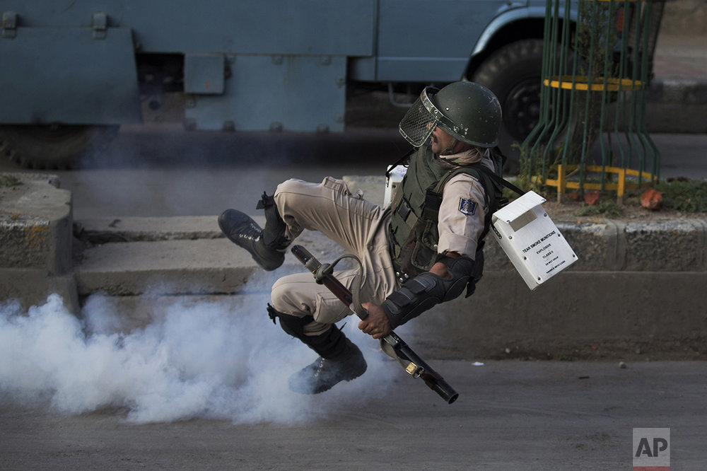 An Indian paramilitary soldier falls as he tries to kick an exploded tear gas shell thrown back by Kashmiri Muslim protesters at the end of a day-long curfew in Srinagar, Indian controlled Kashmir, on Aug. 8, 2016. Kashmir had been under a security lockdown and curfew since the killing of a popular rebel commander on July 8 sparked some of the largest protests against Indian rule in recent years. (AP Photo/Dar Yasin)
