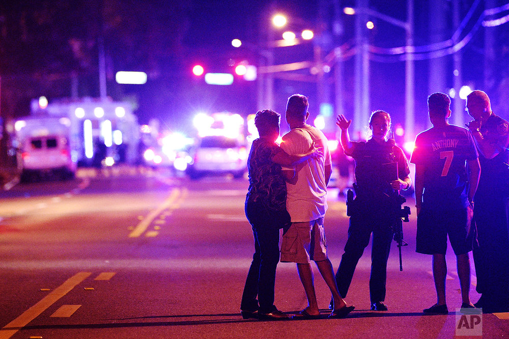 Orlando Police officers direct family members away from a fatal shooting at Pulse nightclub in Orlando, Fla., on June 12, 2016. Omar Mateen, a 29-year-old security guard, killed 49 people and wounded 53 others in the mass shooting. (AP Photo/Phelan M. Ebenhack)