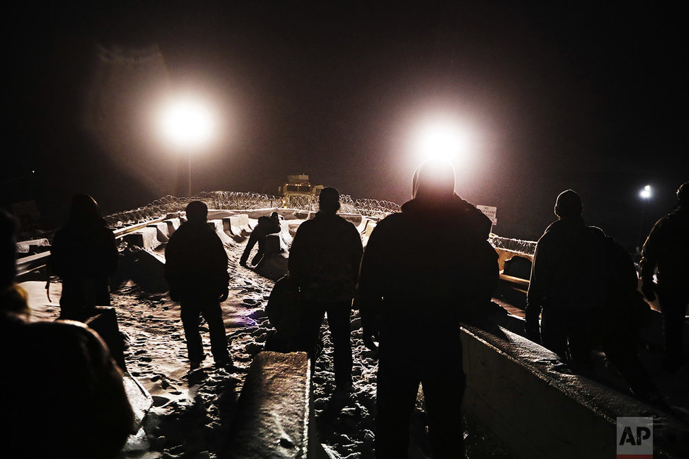 Military veterans walk onto a closed bridge to protest the Dakota Access oil pipeline across from police protecting the site in Cannon Ball, N.D., on Dec. 1, 2016. In a recent clash between police and protesters near the path of the pipeline, officers used tear gas, rubber bullets and large water hoses in sub-freezing temperatures. (AP Photo/David Goldman)