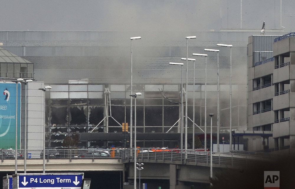 Smoke billows from the Zaventem Airport in Brussels after an explosion there on March 22, 2016. Bombs struck the Brussels airport and one of the city's metro stations, killing and wounding dozens of people, as a European capital was again locked down amid heightened security threats. (AP Photo/Michel Spingler)