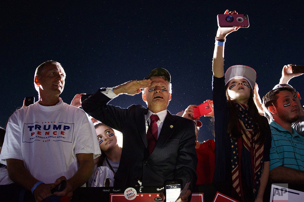 Jeff Muller of Wilmington, N.C., salutes as Republican presidential candidate Donald Trump arrives at a campaign rally on Oct. 26, 2016, in Kinston, N.C. (AP Photo/ Evan Vucci)