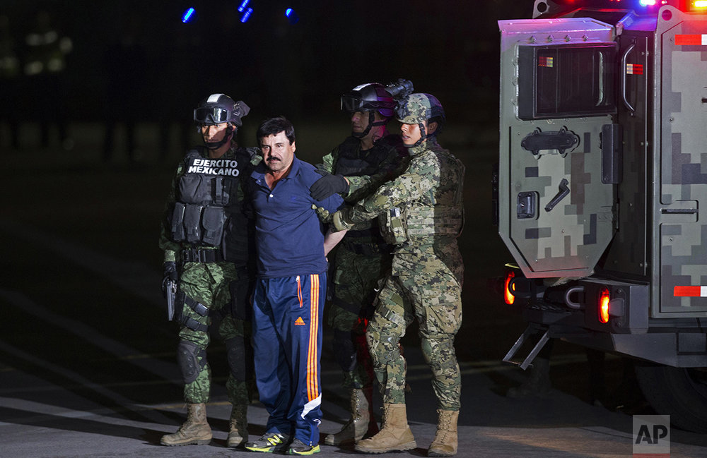 "Mexican army soldiers escort drug lord Joaquin ""El Chapo"" Guzman to a helicopter to be transported to a maximum security prison at Mexico's Attorney General's hangar, in Mexico City, on Jan. 8, 2016. The world's most-wanted drug lord was captured for a third time in a daring raid by Mexican marines, six months after he tunneled out of a maximum security prison in an escape that embarrassed the government and strained ties with the United States. (AP Photo/Eduardo Verdugo)"