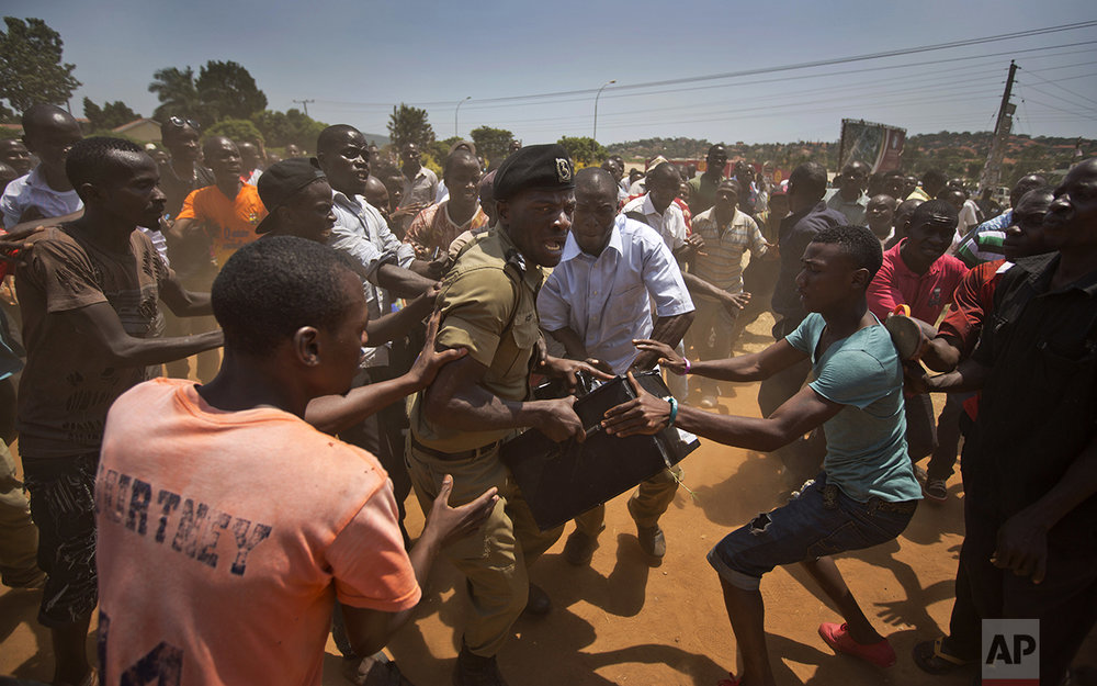 A Ugandan policeman struggles to keep hold of a box containing voting material as excited voters surround him after waiting over 7 hours without being able to vote, at a polling station in Ggaba, on the outskirts of Kampala, Uganda, on Feb. 18, 2016. (AP Photo/Ben Curtis)