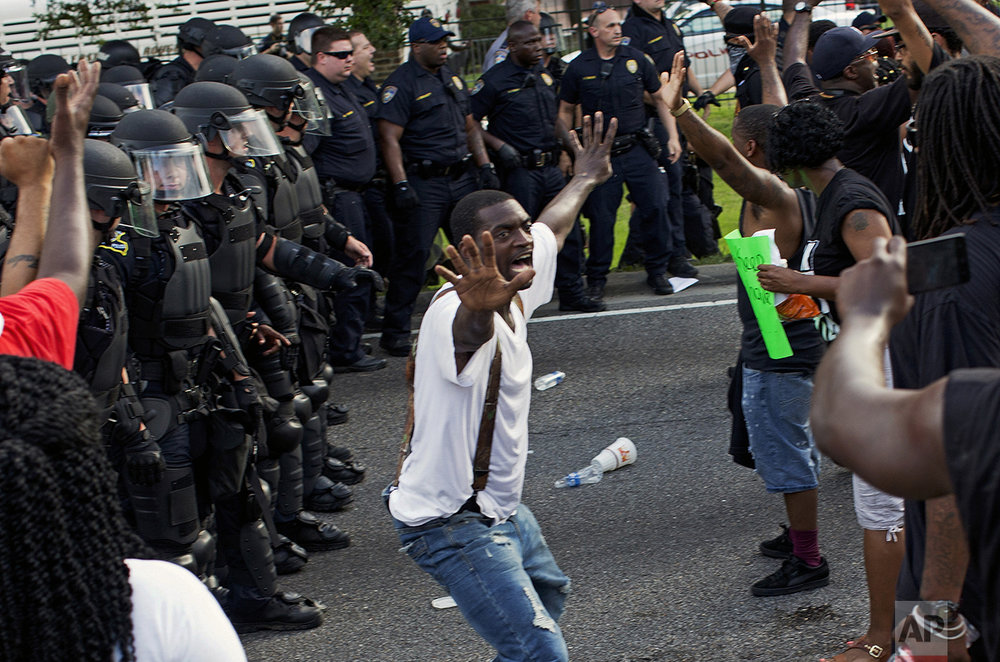 A man attempts to stop protesters from engaging with police in riot gear in front of the Police Department headquarters in Baton Rouge, La., after police attempted to clear the street on July 9, 2016. Several protesters were arrested. (AP Photo/Max Becherer)