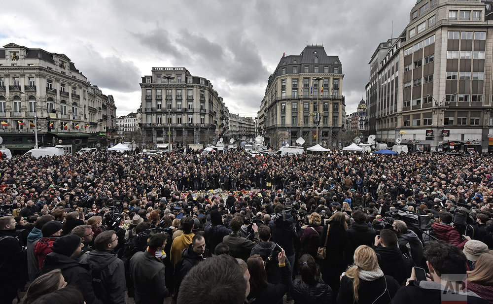 People observe a minute of silence at the Place de la Bourse in the center of Brussels, on March 23, 2016. Bombs exploded the day before at the Brussels airport and one of the city's metro stations killing and wounding scores of people, as a European capital was again locked down amid heightened security threats. (AP Photo/Martin Meissner)