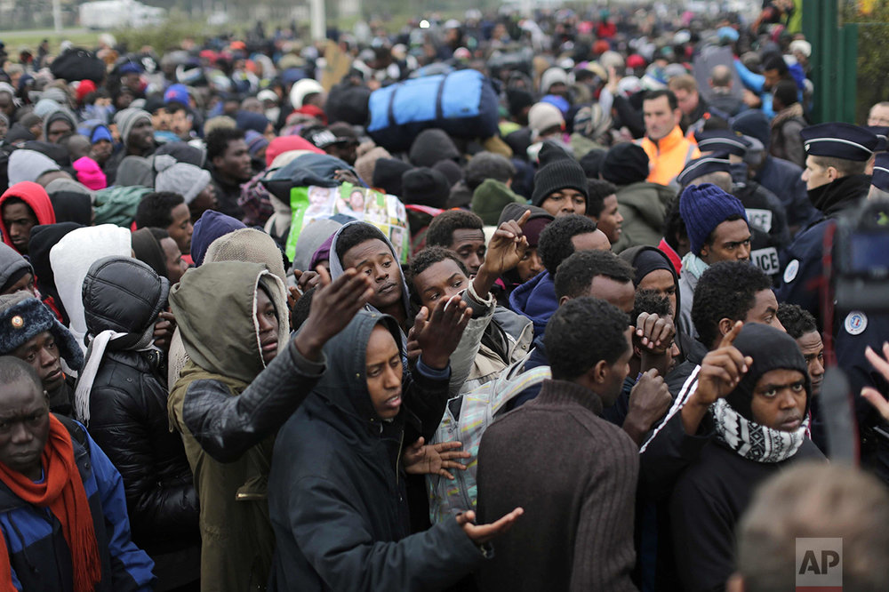 "Migrants line-up to register at a processing center in the makeshift migrant camp known as ""the jungle"" near Calais, northern France, on Oct. 24, 2016. The French evacuated 6,400 migrants from the encampment in 170 buses, starting on Oct. 24, with the intent of resettling them in different regions of France. On Oct. 26 French authorities announced that the camp had been cleared. (AP Photo/Emilio Morenatti)"
