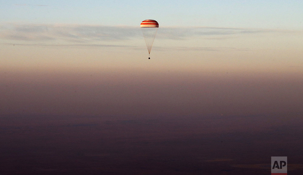 The Soyuz TMA-19M capsule carrying NASA's Jeff Williams, and Russian cosmonauts Alexey Ovchinin and Oleg Skripochka descends beneath a parachute near the town of Zhezkazgan, Kazakhstan, on Sept. 7, 2016. The record-setting American and two Russians landed safely back on Earth after a six-month mission aboard the International Space Station. (Maxim Shipenkov/Pool Photo via AP)