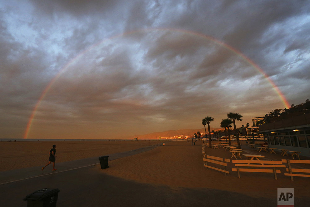 A rainbow appears over the beach and ocean shortly after dawn in Santa Monica, Calif., as one of a series of storms sweeps through California on Oct. 28, 2016. (AP Photo/Reed Saxon)