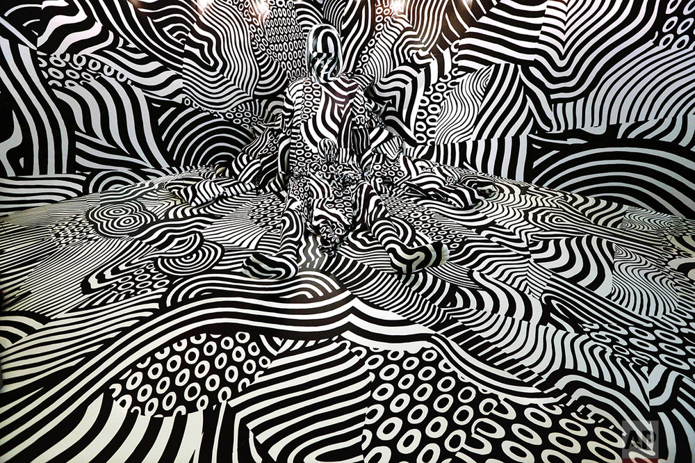 "A model named feebee poses as part of art installation ""Narcissism : Dazzle room"" made by artist Shigeki Matsuyama at rooms33 fashion and design exhibition in Tokyo on Sept. 14, 2016. Matsuyama's installation featured a strong contrast of black and white, which he learned from dazzle camouflage used mainly in World War I. (AP Photo/Eugene Hoshiko)"